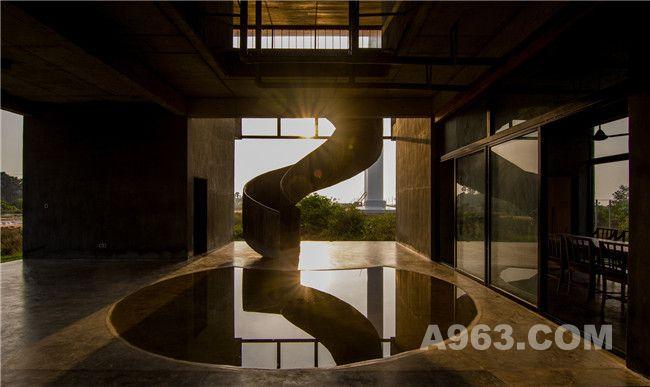 夕阳下的圆形浅水池以及通往二楼的螺旋雕塑楼梯