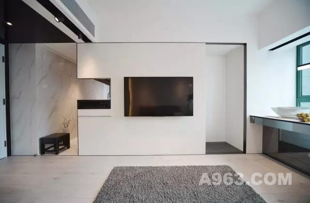 客厅新铺无缝木地板 以几何美学重新打造精致的蜗居感  从厅到房 黑钢也扮演著同一角色 勾划出简洁而不简单的线条轮廓  贯通厨房的电视饰墙 以白色防火胶板对比黑钢 令几何线条尤其突出