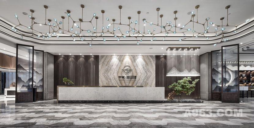 步入前厅,雅致的中式风情和灵透的人文气息融为一体,接待台采用拼纹玉石背景墙面,以植物果实为元素设计的吊灯自由悬挂组合,整体空间通透大气而不乏灵动写意。