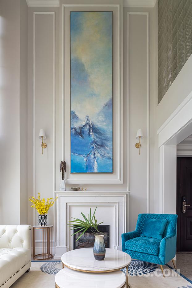 进门右转是会客厅, 中空加壁炉的设计使得整个的房间大气起来,一种贵气自然而然的显现出来,一块蓝色的背景装饰画仿佛给整个房间的色调起了一个主导作用,简约的线条也将其低调的特质凸现出来。跳色的布艺,精致的摆件,艺术挂画打破了整个房间的呆滞,彼此之间又保持着,形态、色彩和谐与平衡。