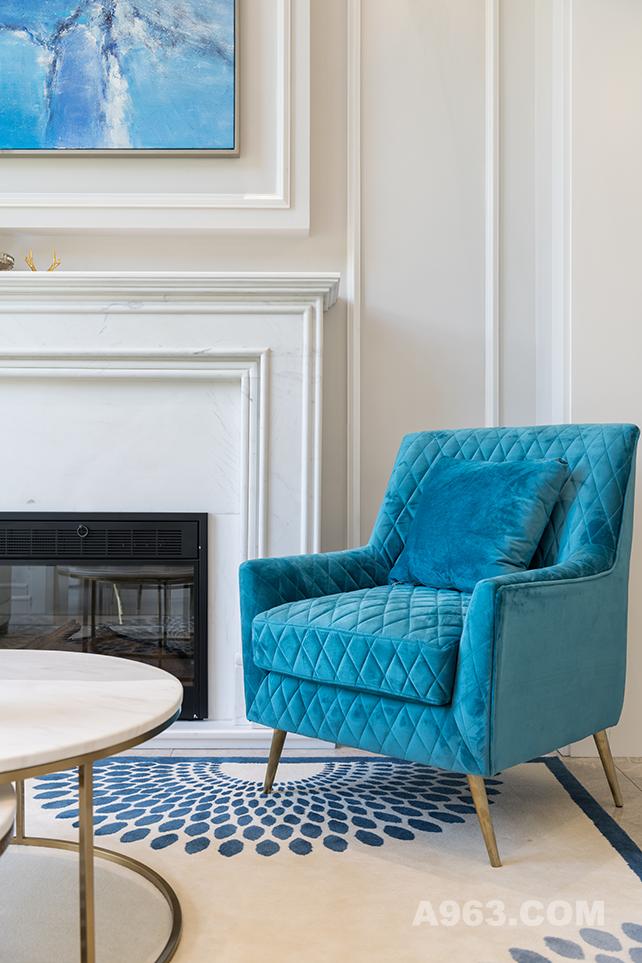 孔雀蓝的单人沙发椅也成了这个空间的一大亮点,摆放的黄色花卉恰好,蓝与黄的碰撞,使得视觉上得到了更大的冲击,妙不可言。