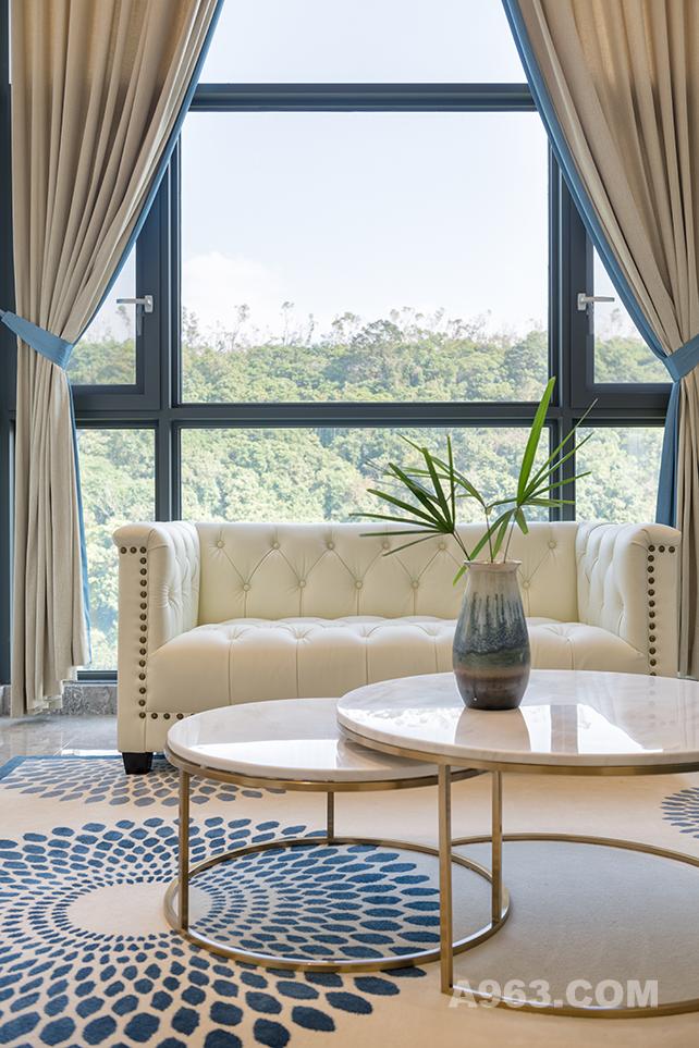 窗外的美景怎可错过呢?透过大大的落地窗,窗外的美景一览无遗,米色的皮质沙发透出了房间的一丝小奢华,再配以蓝色圆形点状地毯,一切仿佛刚刚好。