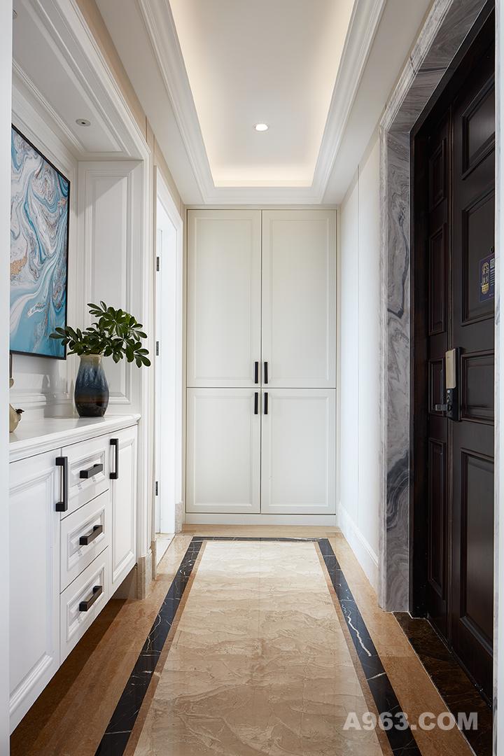 玄关入门便给人一种明亮轻奢的视觉效果。具有品质感的石材门框,开门便印入眼帘的画作,白色木柜合理分区,极大地提高了空间利用性。天花板的吊顶增加了空间的规划感,整体给人一种方正的美感。
