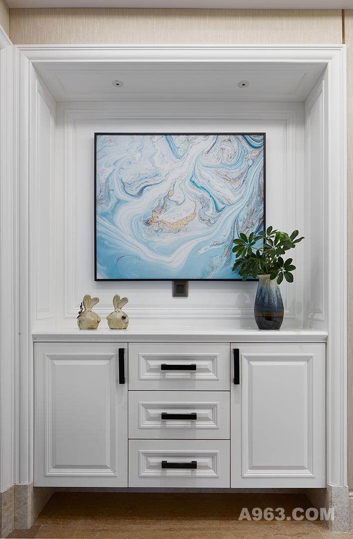 简洁的白色木柜,精致的渐变宝蓝色陶瓷花瓶,金色的兔子摆件体现家装的趣味,随处可见的绿植为这个家庭的居所增加一份生活的写意。方正的格局搭配方正的柜子画框,达到了线条的一致美感。