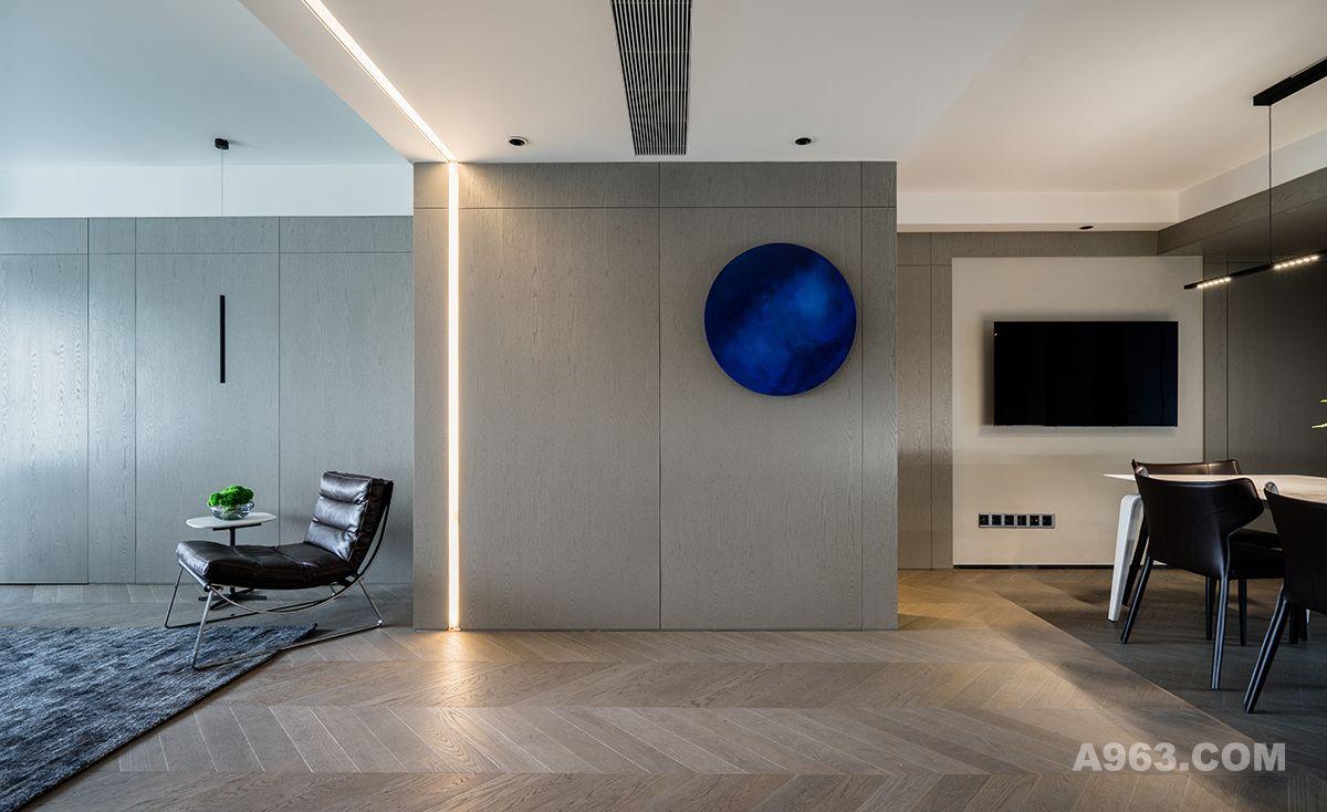 客厅的这个蓝色的装饰物是一副很有故事的装饰画,主要是因为寻找和制作的过程很艰难。设计师的整个空间深化设计完成后就费尽心思在寻找一款点亮整个空间的软装配饰。好不容易托人偶然在国外网站巧遇了这款蓝色物件,可谓是一见钟情了,却没想到到,材质是琉璃的,官方售价要三万多,这个价格实在是太贵了,设计师最后拿着各个角度的照片,到画廊找画师临摹出一副立体画,只用了1000多块,业主夫妇开心极了。设计师觉得从整体效果上也完全达到了整屋的预期效果,非常满意。