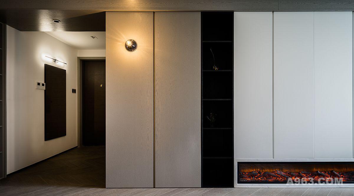原来进门处只是一个门厅,无玄关感,也没有任何设计的区域划分感。进门处增加一面全身镜,在另一侧做了木饰面按压柜面的衣帽柜,延伸过来是从顶到地直通的白色烤漆面板鞋柜。