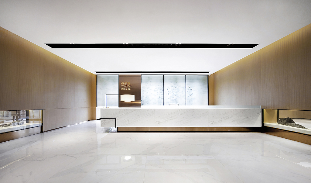 前台接待处是一个企业的形象总集。设计师将景观和室内设计巧妙地融合在一起,力求干净利落的线条与体块的设计关系。绿竹半含箨,新梢才出墙,翠竹的影子投映在背景磨砂玻璃墙上,玻璃橱窗嵌入墙身,石头层叠放置其中产生山脉的起伏感,以现代视角将中式的犹抱琵琶半遮面的含蓄之美展示出来。安静、专注一心、才能安定。
