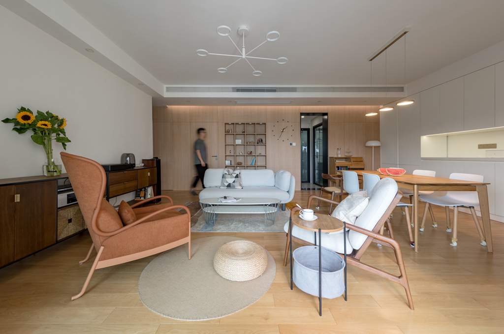 客厅以多功能储物柜的形式取代了传统的电视机,加上整体围坐式布置,巧妙营造出年轻人喜欢的轻松、和谐环境。沙发背面特意做了一面内嵌式展示柜,高度和隐形门一致,宽度比例也极为考究,恰好与沙发居中,远远看去,浑然一体。