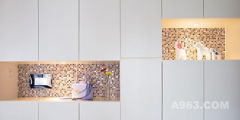 玄关处摒除整片墙面的柜体规划,采用中段留空的设计,搭配隐藏式的灯光,看起来宛如艺廊般的陈列空间。白色的瓷砖、马赛克和高级灰的地板,让玄关不仅仅止于玄关。