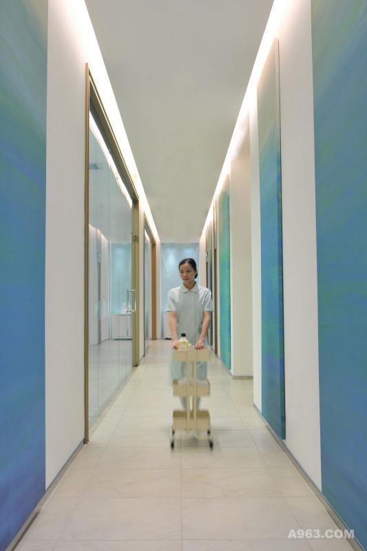 有人说,美,是寻找一种平和。对称设立的隐藏光带实是设计师在空间中不断探讨的平衡法则,以此传递出沉静稳妥的安全之感。单调的白色墙壁未免过于冷清惨淡,于是巧用硬包版画进行装饰,当温润的蓝漫延过整条走廊,仿佛渐变的天空般澄澈爽朗。