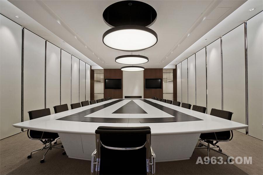 黑白分明的会议桌不仅仅是时尚、现代的代表,也是是简洁、效率的代名词,整个会议室以白色为主,黑色、银色作为点缀,显得时尚大气。从吊顶中延伸出来的独特吊灯使得空间多了一份新意,配合上隐藏起来的灯带造型,满足了会议室对于光线的需求。