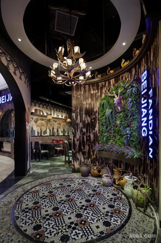 北疆饭店,是一家主打北疆民族特色菜肴的连锁餐厅。为了更好得诠释餐厅的北疆主题特色,设计师首先就在餐厅形象墙上下足了功夫,巧妙而灵活地将具有西域文化特色的元素融入了设计之中。天花板和地面采用圆环元素相互呼应,塑造了空间的统一感。倒掉的烛灯以鹿角作为支架,避开俗套设计的同时,增添了空间的神秘感。