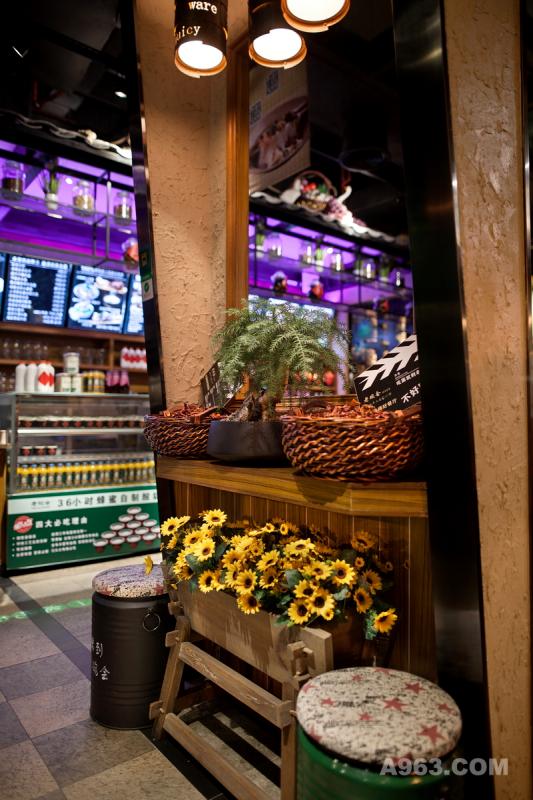 门头形象墙以花卉、绿植、辣椒作为装饰,搭配粗糙质感硅藻泥墙,于自然气息中透露着乡土风味。中空窗形让内外空间形成层叠之势,各个区域景观进行分区营造且富有层次。