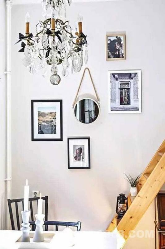 楼梯的墙壁上挂了各式各样的装饰物,让白色的墙壁看起来不单调。还有和简洁时尚相比有点浮夸华丽的吊灯。