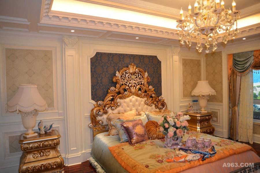 此房间为主卧室,干净素雅的墙板做背景,配合巴洛克风格的床头与床头柜装饰,使整个空间弥漫着雍容华贵的气息,更加的突显帝王之气。