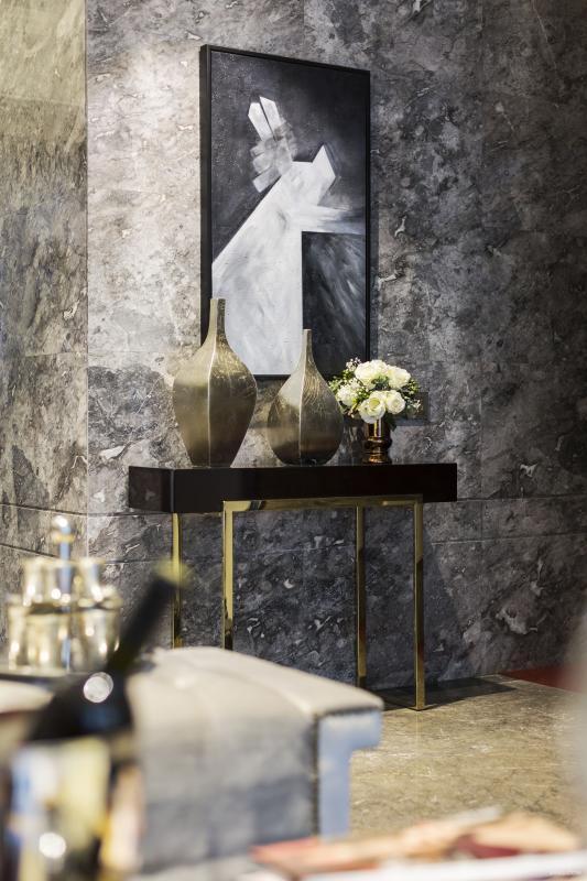 玄关从一幅抽象画拉开序幕,几何构图画面,有人说是建筑,有人说是动物,不管是什么,设计师要的是它的构图与玄关柜呼应,简单的玄关台,金属搭配增加它的奢华感。 意大利帕高灰大理石墙面,与餐厅黑镜墙面呼应,配上高档的水晶吊灯,跳舞兰点亮整个空间。
