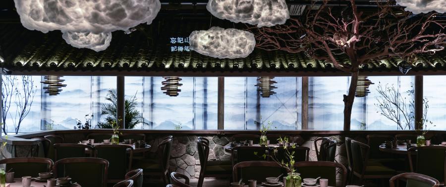 一个开敞的大院子,天顶喷黑从视觉中隐退,漂浮于天花的棉花云灯,仿佛似云轻浮于天空中。大院子周围用原始石材砌筑,粗与精的材质肌理对比。