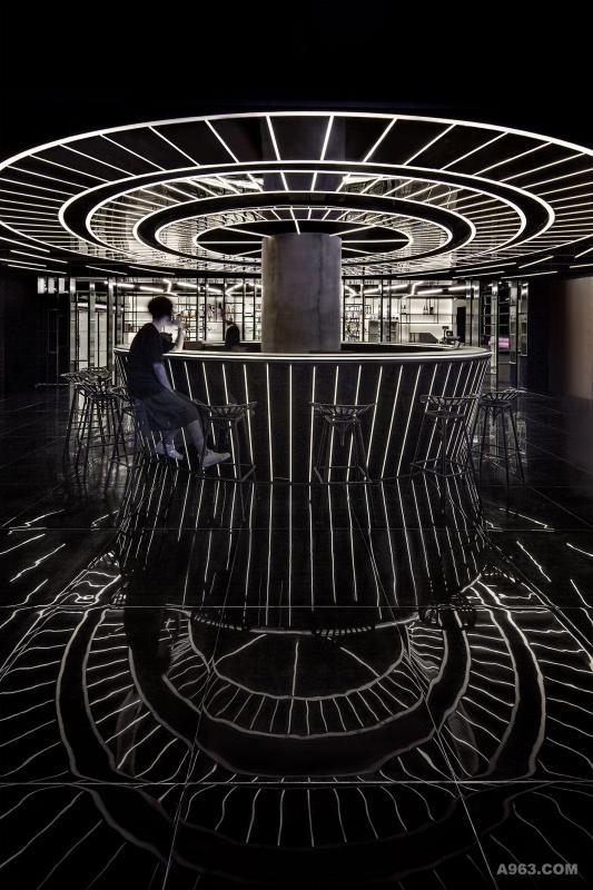 """大堂服务台 我们称之为""""圆盘""""的服务台是大堂空间的焦点。地面选用高反射材质使它更具气势与张力。服务台与其天花本身的材质为黑色镜面不锈钢和线形灯,本身非常精致并且散发着自然的光晕。"""