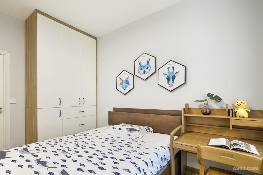 男孩房的床头背景是浅蓝浅蓝的艺术涂料,健康环保; 在软装搭配上采用卡通挂画和床上用品,带给小男孩活泼充满童趣的空间。