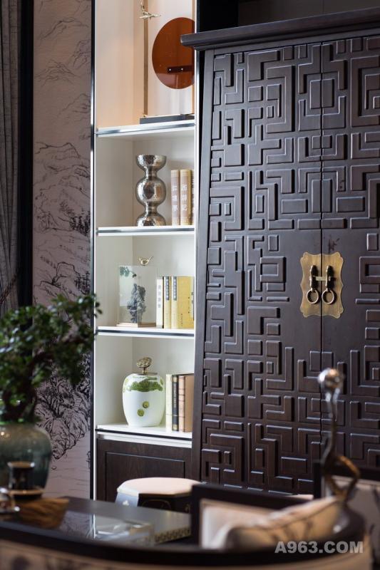 背景陈列架以浅色木饰面结合钢制成,精致而不失实用功能。中间的大实木柜,既可以是表现古色古香的中式气质的一种符号,又可以是为收纳考虑而设计的装饰柜体。