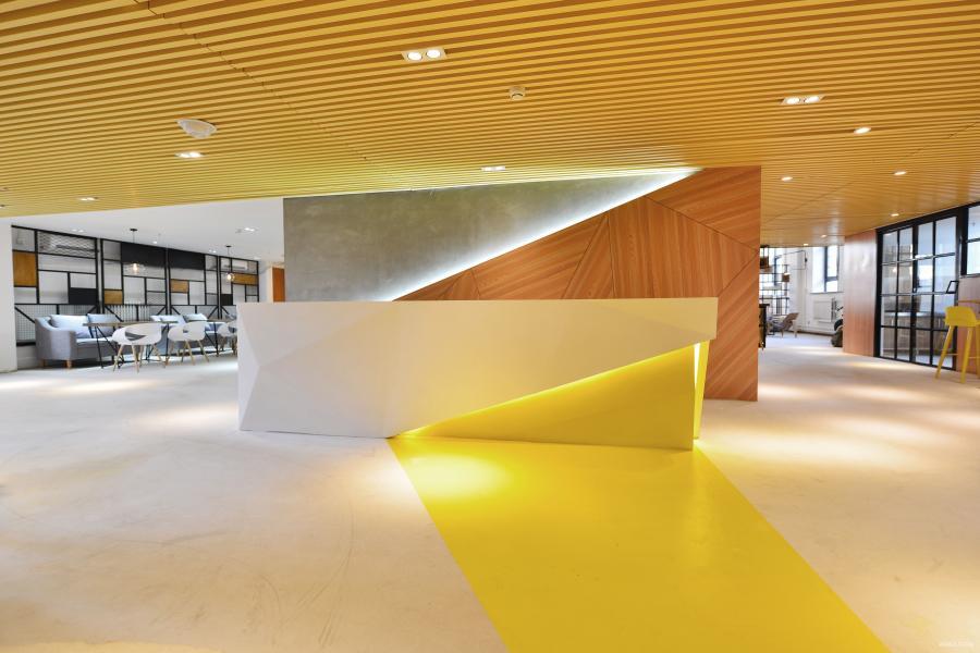 从一进门是一个几何切割的前台,它的右下脚做了一个开放式的缺口,仿佛一束温暖的阳光从吧台底下洒出来一直延伸到地面。前台的左右两边的动线分别是进入大办公区的动线布置,一楼布置了大办公区、会议室、后台办公区、会客厅、咖啡吧台区、休息区、茶水间。
