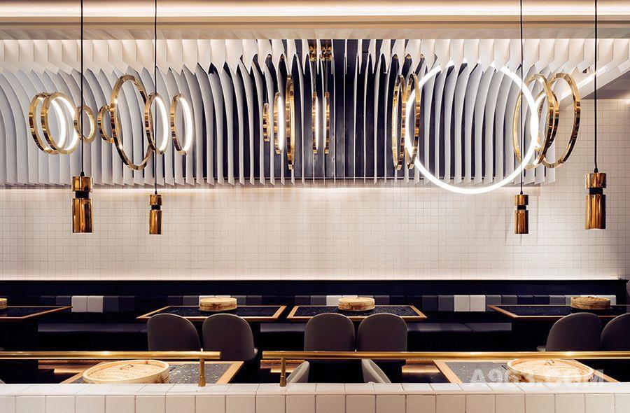 空间整体由曲线和直线线条构成,设计师巧妙地利用灯光效果,搭配金属质感的圆环装饰,打造出一种灯火阑珊的视觉体验。