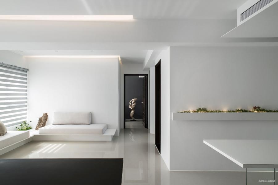 簡約客廳,白色系木作體、白烤玻面材和米色布料沙發座墊構成素淺基色背景。