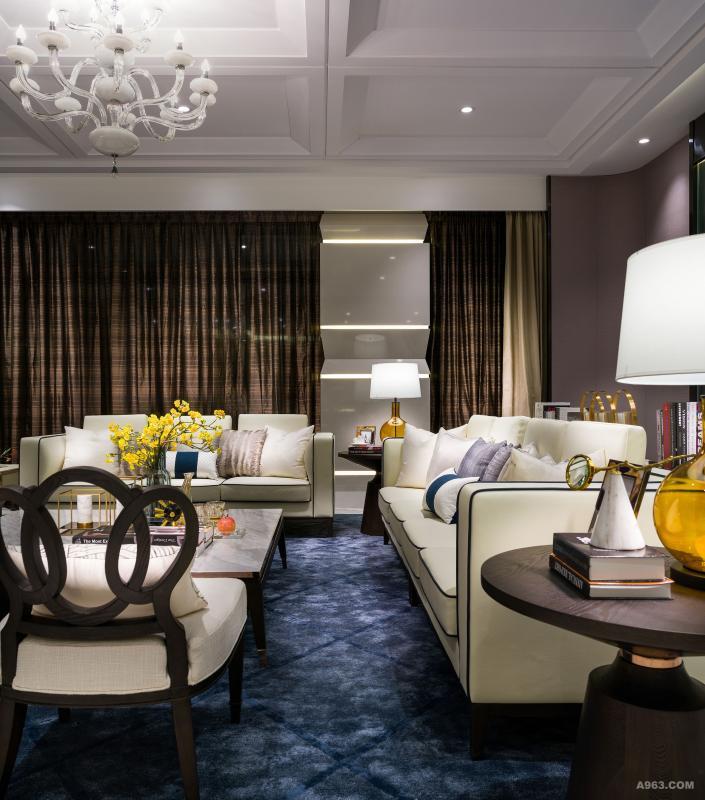 客厅:以米色为主调,在条子坑纹玻璃为主题牆前及深啡缀灰蓝色地毯上,摆放着米白色沙发、单人座椅及云石枱面茶几,在经典的水晶灯映衬下,洋溢一片华丽时尚的光芒。