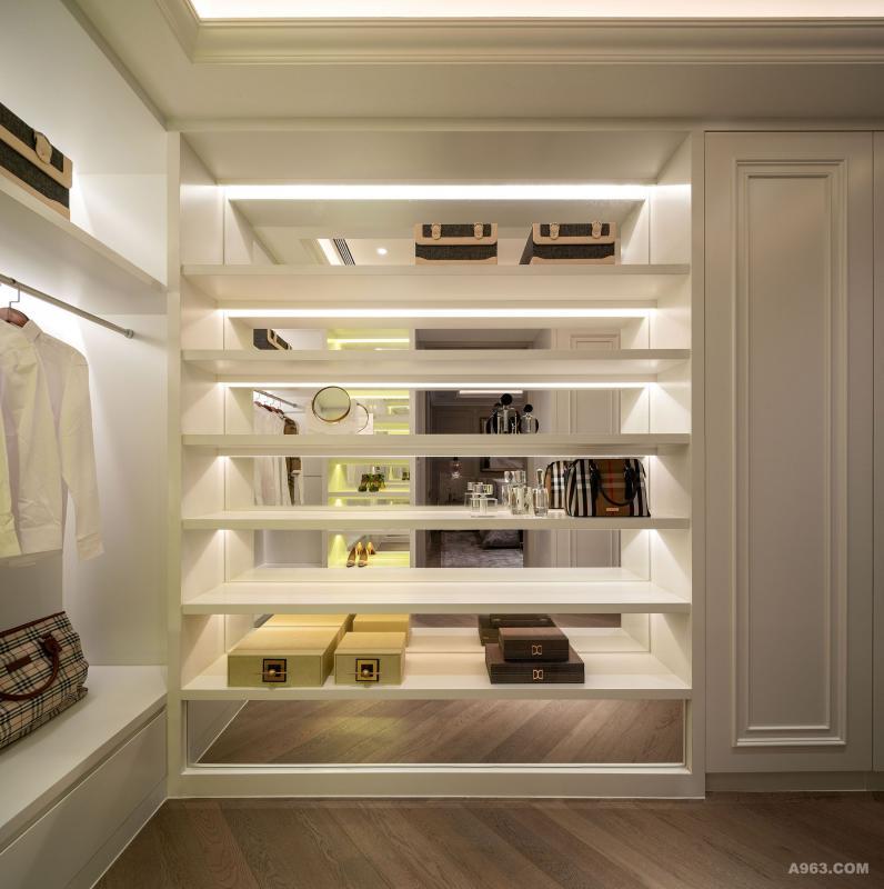 衣帽间:木纹地板配合米白色的墙身和收纳柜,柔和的黄色照明,整个空间都让人无比放松;具收纳和装饰于一体的入墙柜,既耐看又实用,尽显住户的优雅独特的品味。