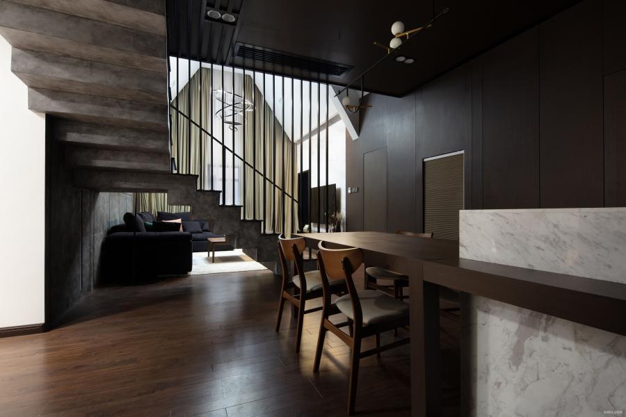 在设计了七八个版本过后,得到了最后呈现的这个设计,既能在上楼的时候避免撞梁的问题,又有足够的空间放置楼梯的位置,在这个基础上还解决了客厅直对入户门的问题。在视觉效果呈现上楼梯扶手采用竖条方钢,既美观,又能当玄关隔断用。