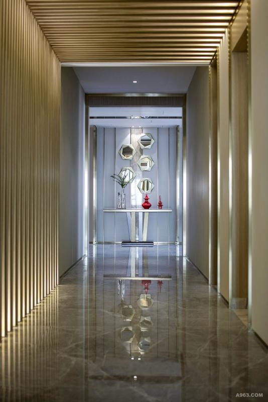 转而进入私密的居室区。       隐喻编织起的回廊,回廊中斑驳的光影与墙面现代的米白色皮革相结合,形成流畅的动势,犹如时光长廊,由此将来人引入居室。