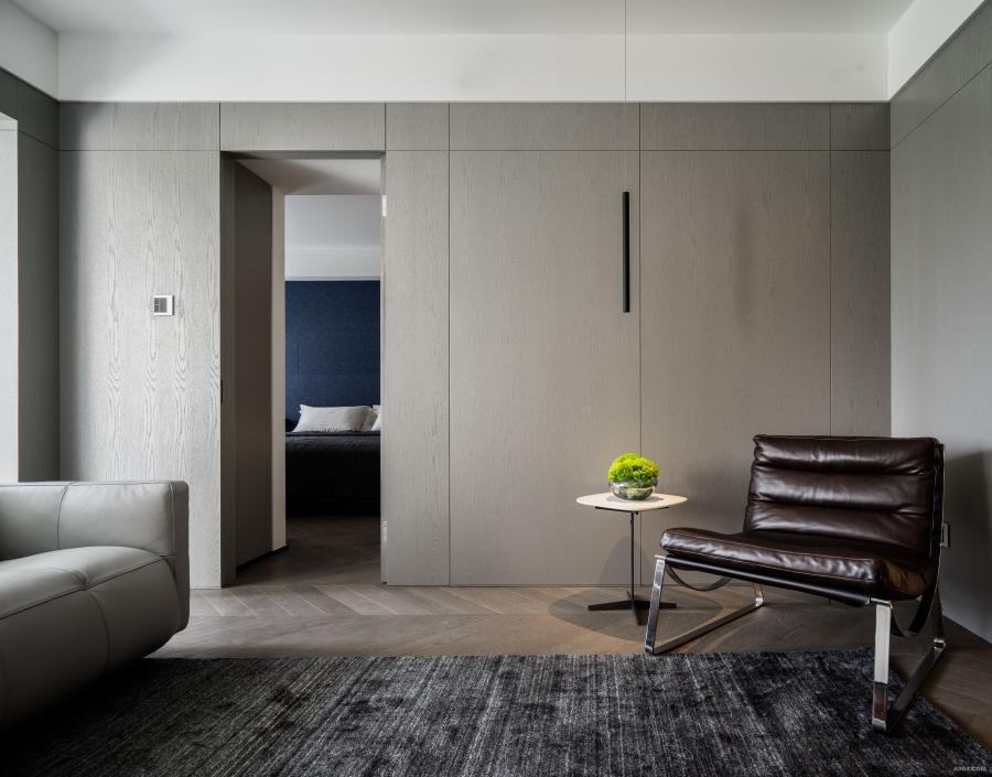 设计师为业主精心海淘了一款兼颜值与功能并存的沙发,并且可以活动摆放。因为后方的灰色正面木饰面墙体还有着通往主卧的隐形门,所有的面板切割比例都是跟着门的宽度走的,整体感很好,块面清晰,维和感强。