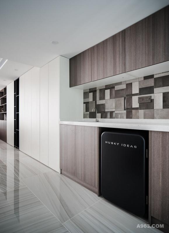 地下室茶水间连接衣柜设计,也是开放式的。从型上而言,类似于厨房台面与上下柜,拥有厨房部分功能性;从质而言,选用与影音空间的书柜同种颜色材质门板,构成呼应关系。该处也是健身空间,下柜内嵌一个HUSKY IDEAS制冷剂,方便业主运动过后饮水休息,无需到一层厨房冰箱取水。
