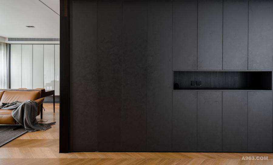 进门大储物柜高度有2.8米,品牌是德禄雷尼尔,面板选用的是黑色带暗纹的模压板。整体空间都是黑白为主的简约色调,地板是宅匠的,全屋采用鱼骨拼,橡木/实木复合,属于小众国产。