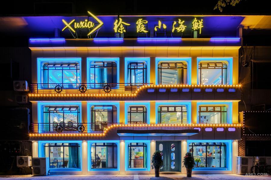 整个外立面以船舱的造型来表现,运用冰蓝色和黄色的灯光加以亮化,分出各个层次的立体感。落地铝合金窗格上部设计了翻窗,增加室内通风的同时,外部空气进入不会影响就餐的客人。