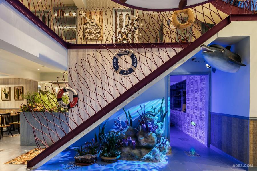 舷梯下设计了一组珊瑚岛礁的海景,在水纹灯的照射下增加了海景动感,海豚的出现为空间增加了新亮点。