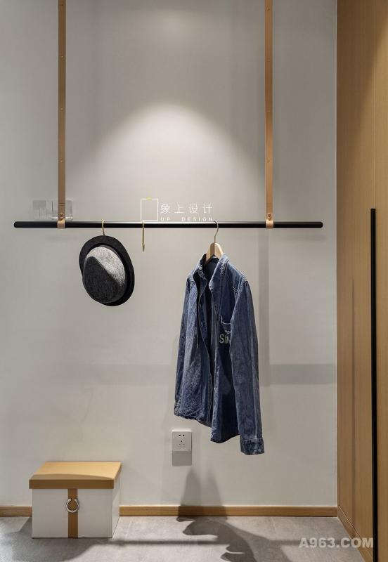 哑光白色墙面、水泥质感的地面呈现干净整洁的界面,使得浅色的木饰面融入空间自然而又温度,设计师从实用出发精心设计,为满足屋主一家人的物品收纳,用心挑选的吊挂置物架,塑造出平和转换优雅的节奏感。并于顶端装置射灯,透过光源晕染更显层次感。