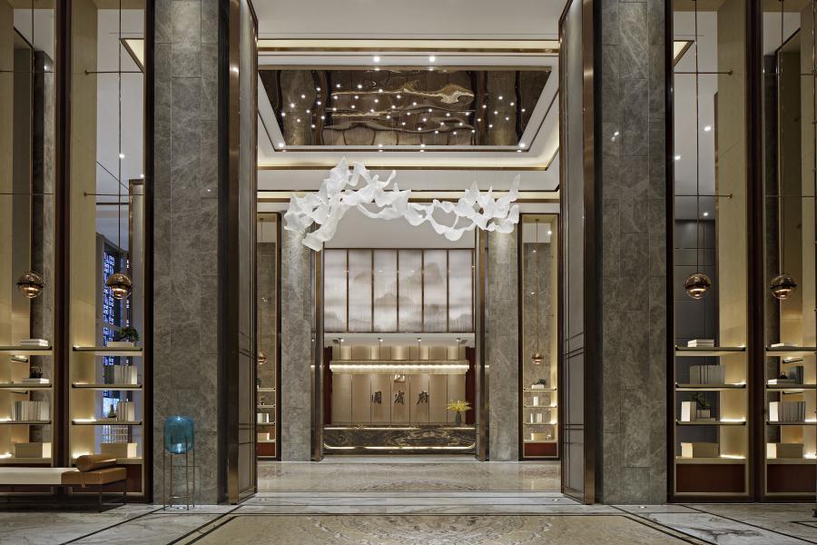 入口门厅在布局上讲究对称,强调元素的秩序感展现稳重大气的格调风范。迎面看到的是气派的博古架,顶天立地,区分空间,起到欲扬先抑的效果。极具视觉张力的大型吊灯,优美流动,与山水背景动静相宜,光彩交织,尽显东方独有的品质感与仪式感。