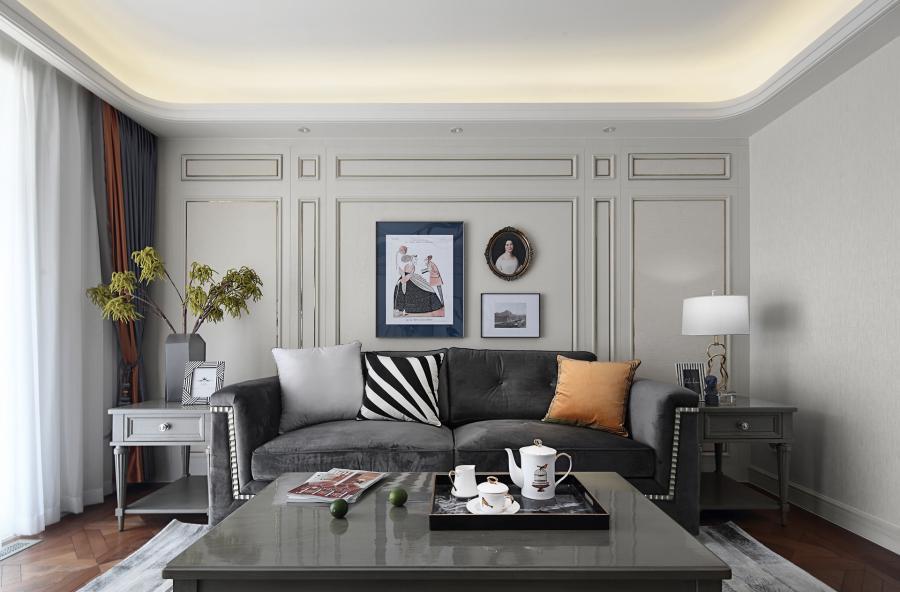 客厅背景墙上的一组装饰画是现代与复古结合的碰撞,突显出室内浓厚的韵味。沙发不经多余的修饰,深灰色的搭配稳重、考究,中间嵌入的扇贝型木条简约时尚如海面的波纹,提升空间独特的格调和品位。