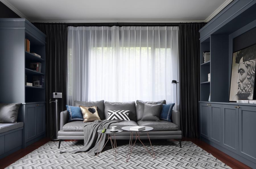 客厅居中放置了三人座的灰色皮质沙发,时尚有范。沙发背后是一个大窗户,安装的是落地帘,光线透过细细的薄纱照射进来,明亮的光线能成功打破屋内的暗色,给人一种明快的感觉。地上搭配了黑白灰的鱼骨造型地毯,增加了视觉的延伸感。