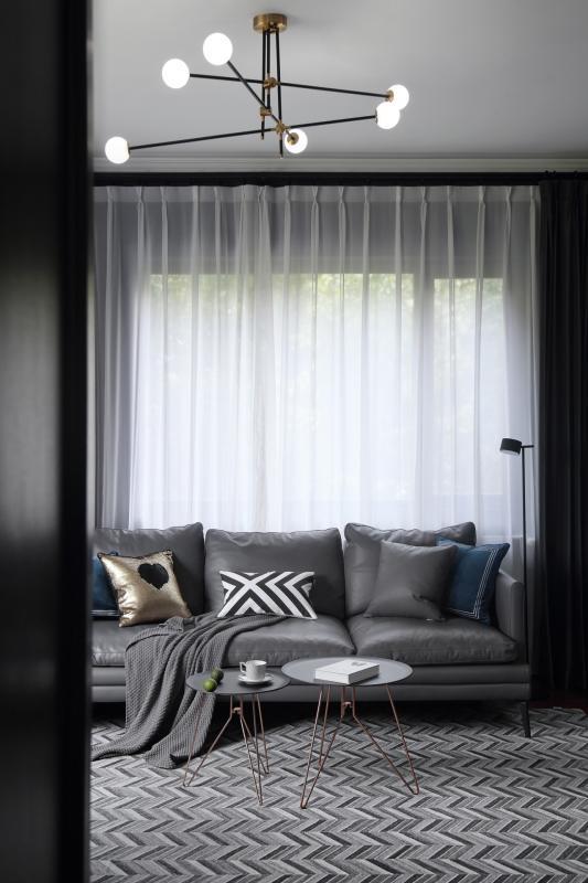 客厅选购的魔豆吊灯搭配了黑色与金色两种颜色,采用了长短杆交替的设计,可以增加空间的层次感。沙发旁的落地灯拥有纤细的柄杓,灯罩顶端可以调节光源,内敛不张扬,以小细线之美,提升了空间的质感。