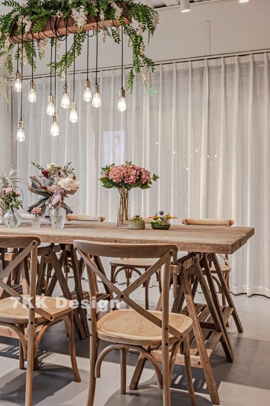 上方艺术吊灯搭配简约森系原木桌椅很有意境,长形桌子除了展示也作为手工台使用,上面摆满了不同品种的鲜花,每一束都是主人亲自搭配的艺术作品。