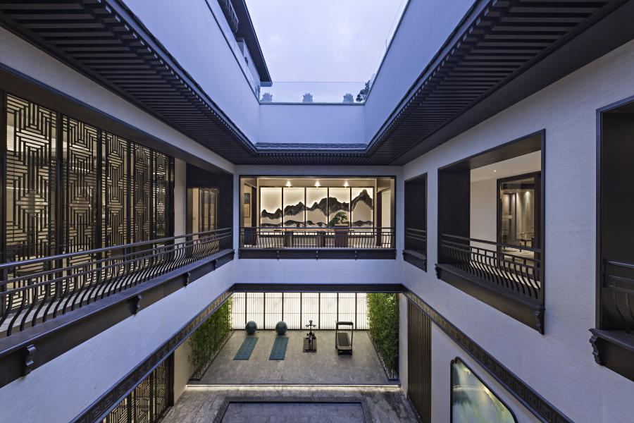 负一层围绕中庭花园增设空中廊道半室外空间,减缓地下9米的落差感,将外部的清风明月引入室内,同时也是负二层的遮阳屋檐,增添了生活的志趣。