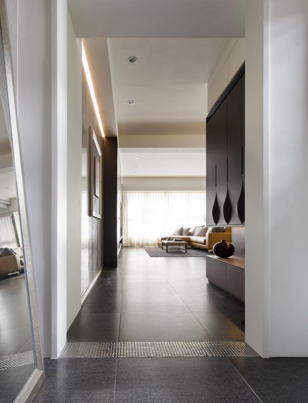 玄關處採用與客廳相同的深灰色大理石。為了區分裡外,特意在門框對應的地面鋪設銀色馬賽克磚,巧妙又別致。入口左手邊的落地鏡方便屋主整理儀容,踏入玄關後,右邊則設有大片置物櫃。其流線型把手別具匠心,上下櫥櫃之間則留出展示區,預示這個家中濃厚的藝術氣息。