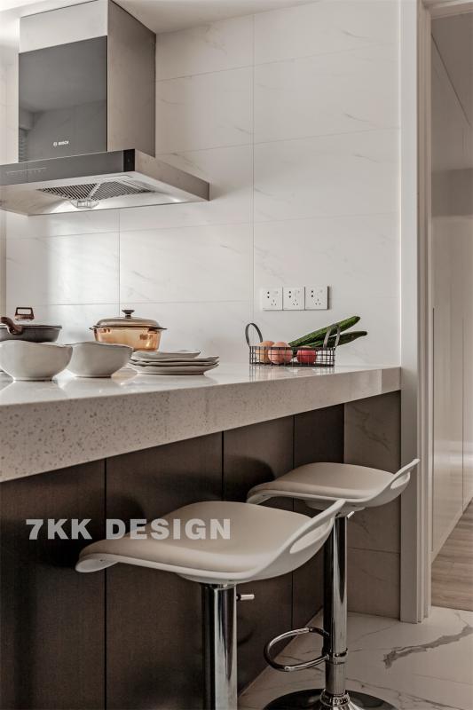 吧台采用水磨石台面,烧完的饭菜随手摆放很方便。台面下方做成柜体形式,为小小的厨房空间增加更多的收纳功能。简约高脚凳搭配,早晚餐可以很方便在吧台解决。