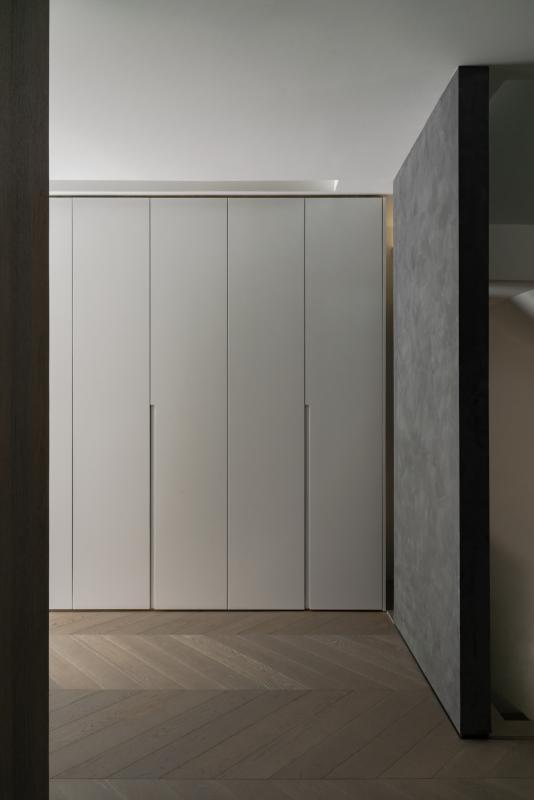 入户玄关,又可作为半开放式储物间。在空间中设置了大量的柜体,作为至简的内核。 柜门设计尽可能隐藏起来,简化了顶和地面的收口条,拉手做内嵌设置,携物通过时没有遮挡物。
