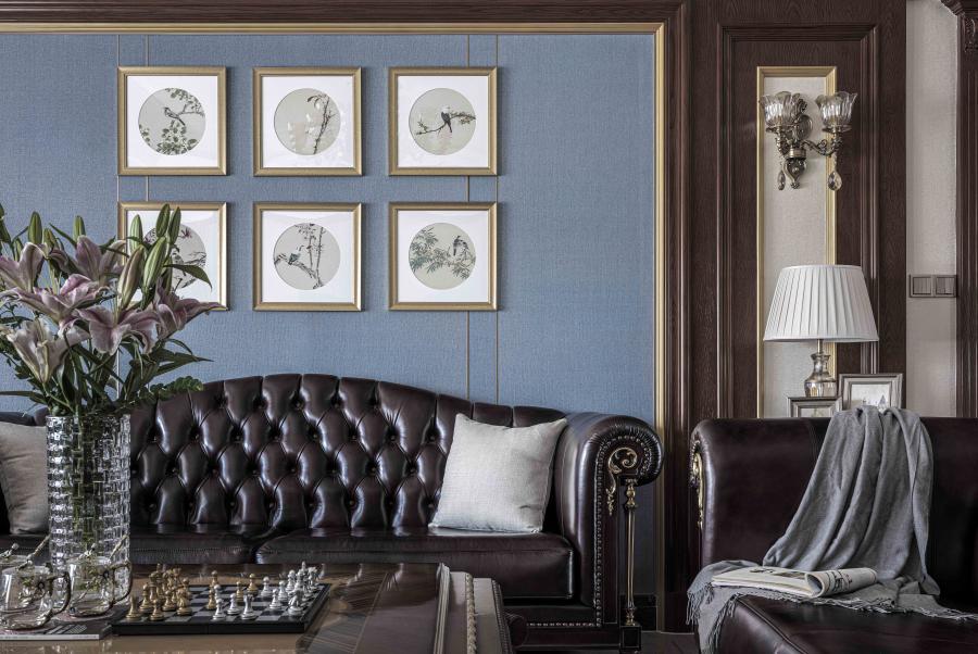 优雅的蓝色沙发背景穿插,配以金属质感的包边,中式风格的挂画与中式风格的地砖点缀,营造了中西结合的轻奢感,且不乏素雅,艺术不分国界得以表达。