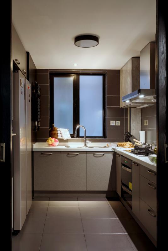 餐厨间选择用一道黑色推拉门作隔断,烹饪时关上隔绝油烟,完全推开后可以隐藏在墙缝内,视线开阔,空间更为通透。从推拉门进入厨房,使用了白色台面的L型洗、切、炒区域动线合理,操作时很是方便。