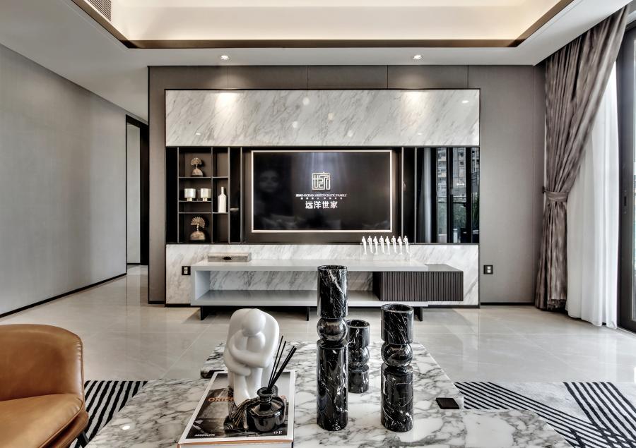 地面上铺带有大理石纹理的地砖与电视背景墙相呼应,凸显整个空间的大气与明亮,沙发背景木饰面的装饰,中和大理石的冰冷与坚硬,增添一丝温暖的气息。