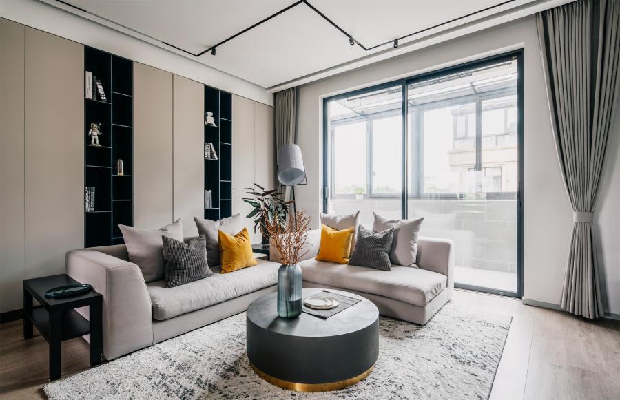客厅不再选用独立灯作为主要的照明来源。黑色轨道在顶面产生几何图形,丰富了顶面的格局。